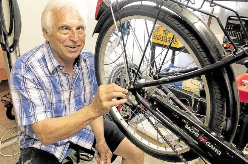 Gerd Müller repariert Fahrräder mit Geflüchteten