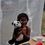 Glückliches geschminktes Kind umarmt Stoffpanda